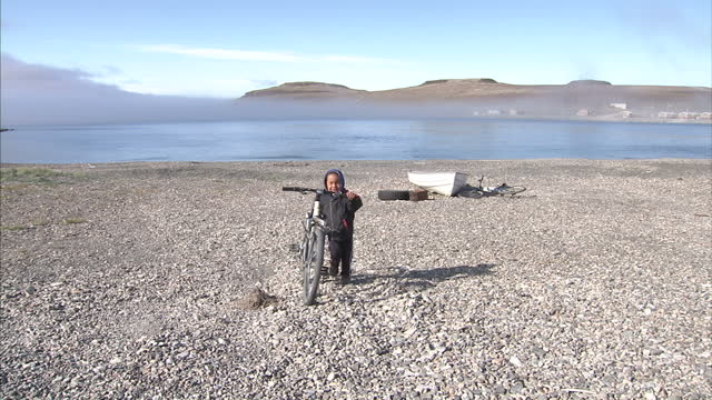 vídeos de stock e filmes b-roll de exterior shots of a inuit child pushing a bicycle on pebble shore on august 25 2007 in cambridge bay canada - inuit