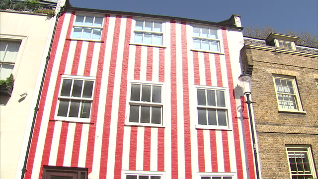 exterior shots of a kensington townhouse painted in red and white stripes as passers by stop to take photographs of it on april 15 2015 in london... - offbeat stock videos and b-roll footage