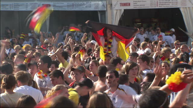 stockvideo's en b-roll-footage met exterior shots of a large crowd of german football fans in fanzone watching on a giant screen cheering and celebrating as the final whistle goes in... - duitsland