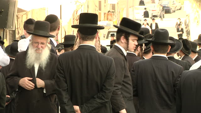 stockvideo's en b-roll-footage met exterior shots of a large crowd of orthodox jewish people gathered in a jerusalem street for the funeral of rabbi yeshayahu krishevsky who was killed... - orthodox jodendom