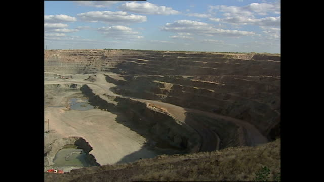 exterior shots of a large open cast diamond mine in botswana as large dump trucks remove rock for crushing on june 07, 2001 in unspecified, botswana. - retrovirus video stock e b–roll
