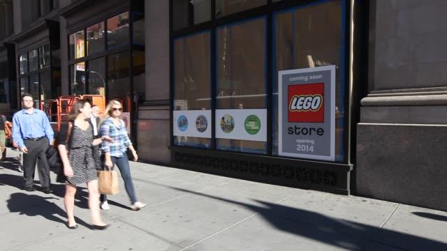 Exterior shots of a Lego sign outside the new Lego store set to open in the Flatiron District in New York NY US Commuters walk past a Coming Soon...