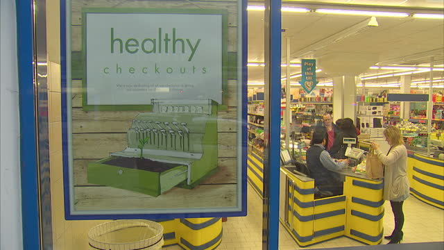 exterior shots of a lidl supermarket including a large poster in the store window announcing lidl's new 'healthy checkouts' scheme which will remove... - checkout stock videos & royalty-free footage