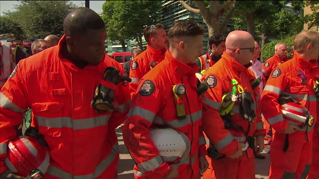 Exterior shots of a line of firefighters observing a minutes silence outside the remains of the Grenfell Tower on 19 June 2017 in London United...