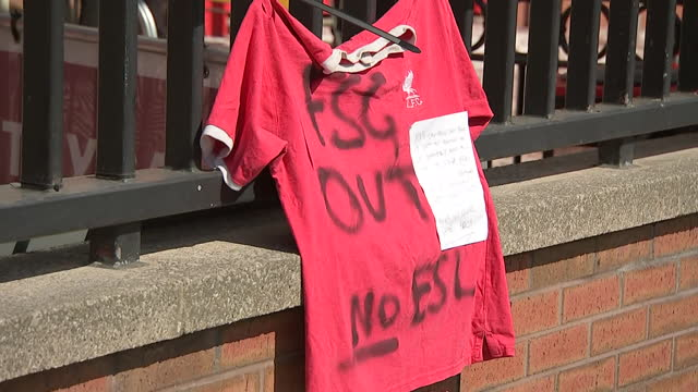 exterior shots of a liverpool fan tying a red shirt to the gates outside anfield with the words 'fsg out no esl' graffitied over the top and a letter... - shirt stock videos & royalty-free footage
