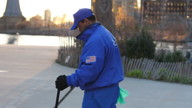 exterior shots of a local authority park keeper sweeping up rubbish in a brooklyn public park with the hudson river and manhattan skyline in the... - sweeping stock videos & royalty-free footage