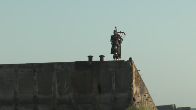 exterior shots of a lone piper pipe major trevor lily on a section of the mulberry harbour in arromanches markig the moment a british soldier landed... - d day stock-videos und b-roll-filmmaterial