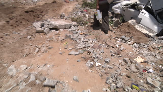 exterior shots of a man and woman walking through a devastated area of gaza carrying a few of their belongings, past a completely destroyed bus,... - パレスチナ自治区点の映像素材/bロール
