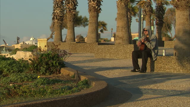 exterior shots of a man strumming a guitar on the seafront in ashkelon on march 16 2013 in national harbor maryland - ashkelon stock videos and b-roll footage