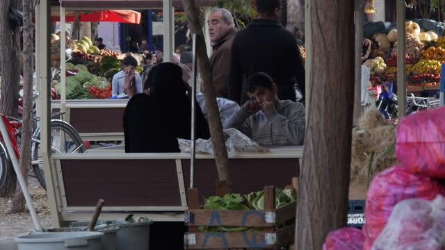 exterior shots of a market selling fresh produce and women wearing hijabs walking along the street on december 2, 2015 in kilis, turkey. - 僧衣点の映像素材/bロール