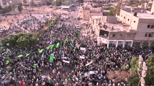 stockvideo's en b-roll-footage met exterior shots of a mass rally in centre of tripoli in support of colonel gaddafi with protesters waving green libyan flags mass rally in support of... - libië
