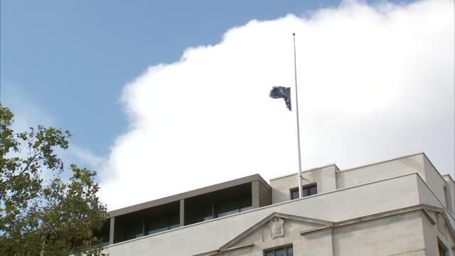 exterior shots of a metropolitan police flag flying at half mast over the new scotland yard building after the fatal shooting of officer matt ratana... - 銃犯罪点の映像素材/bロール