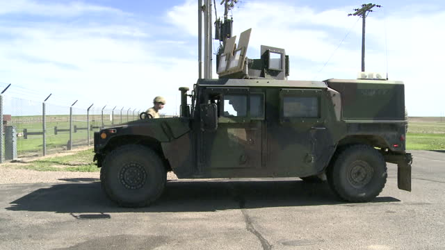stockvideo's en b-roll-footage met exterior shots of a military humvee driving on patrol on the fe warren us air force base an active nuclear missile bunker on 1 june 2017 in wyoming... - massavernietigingswapens