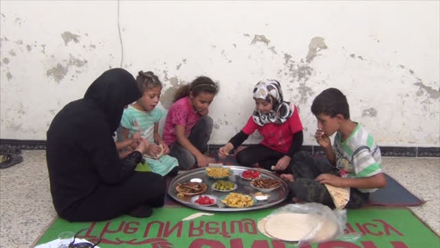 exterior shots of a mother in aleppo with her four young children sat down to eat a traditional meal on august 24 2016 in aleppo syria - family with four children stock videos & royalty-free footage