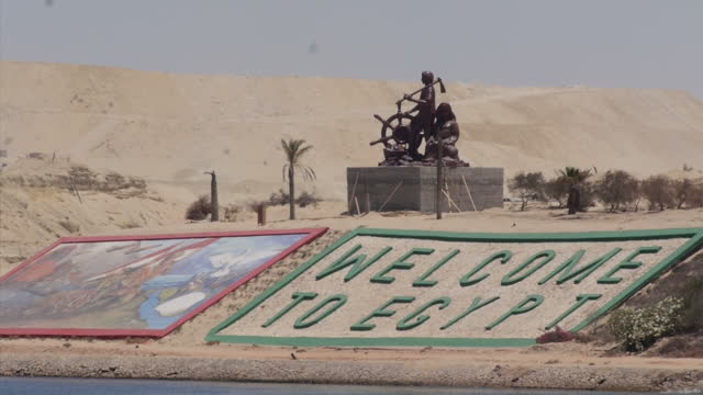 exterior shots of a new dock area on the suez canal with 'welcome to egypt' and 'welcome to safe egypt and its secure canal' signs and general... - suez canal stock videos & royalty-free footage