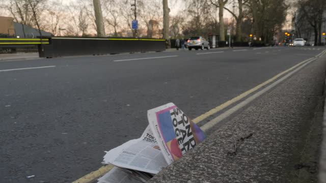 exterior shots of a newspaper in the street gutter with the headline 'london stand together' in westminster on 25th march 2020 in london, england - dividing line stock videos & royalty-free footage