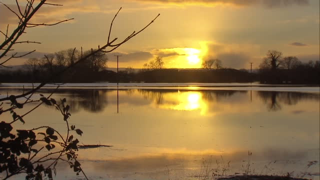 exterior shots of a pair of swans swimming on flooded farmland and the sun setting above flooded fields flooded fields in somerset on january 04 2014... - pair stock videos & royalty-free footage