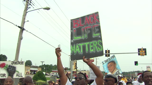 exterior shots of a parade through the sterets of ferguson marking the first anniversary of the michael brown shooting with protesters carrying... - police brutality stock videos and b-roll footage