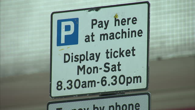 exterior shots of a parking warden walking along a london street a 'pay and display' parking ticket machine at the side of a street and street signs... - parking ticket stock videos & royalty-free footage