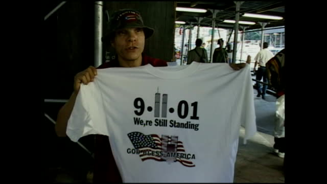exterior shots of a pavement vendor selling 9/11 tshirts reading 'we're still standing' on september 24 2001 in new york city - petronas twin towers stock-videos und b-roll-filmmaterial