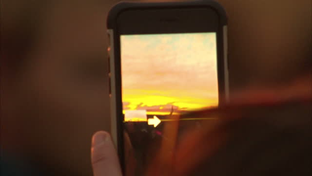 vídeos y material grabado en eventos de stock de exterior shots of a person capturing a panoramic photograph of the sunrise at stonehenge on an apple iphone during summer solstice celebrations.>> on... - solsticio de verano