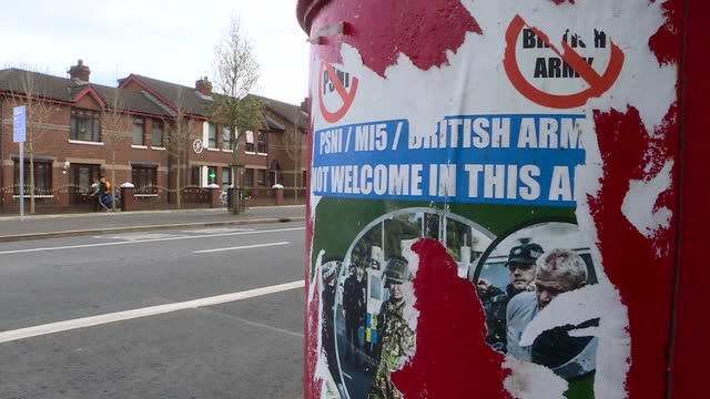 Exterior shots of a poster on a street lamp partly ripped down reading 'PSNI MI5 British Army not welcome in this area' and exterior close up shots...