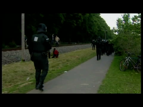 exterior shots of a procession of riot police arriving riot gear marching along path