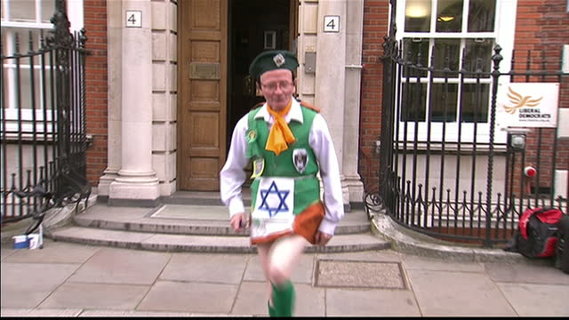 Exterior shots of a protester dressed in an Irish costume with a bonnet and kilt and Israeli Star of David on his chest dancing in front of the...