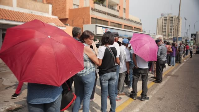 exterior shots of a queue of bank customers outside a branch of bfc bank waiting to withdraw their money on 8 march 2019 in caracas, venezuela - venezuela stock videos & royalty-free footage