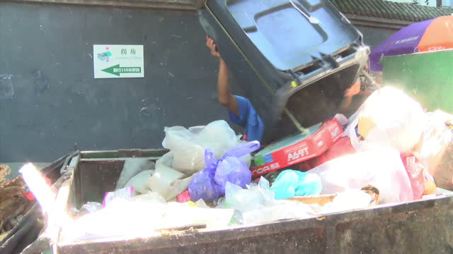 exterior shots of a refuse collector at work in a beijing alleyway collecting rubbish in a small skip on september 01 2015 in beijing china - 2010年代点の映像素材/bロール