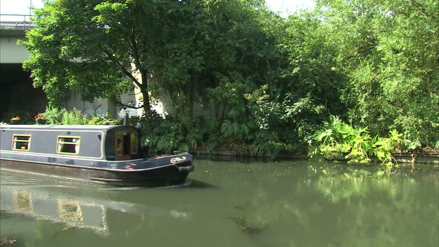 exterior shots of a river boat river barge narrow boat sailing down a canal on july 18 2015 in unspecified united kingdom - galeere stock-videos und b-roll-filmmaterial