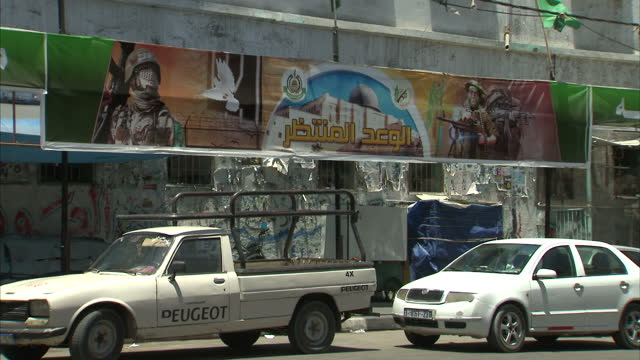 exterior shots of a road junction in gaza city and hamas murals depicting fighters holding rockets and guns as an imam's speech plays out from the pa... - 表す点の映像素材/bロール