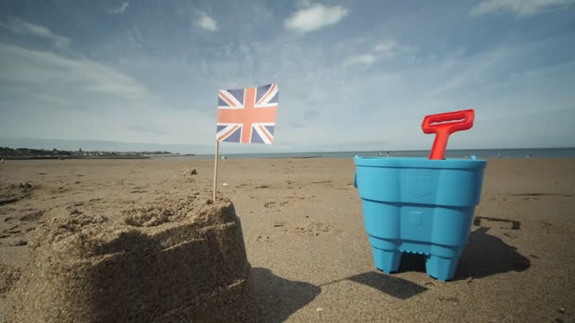 GBR: UK: British Holiday Stockshots with sandcastle and flag of the Union on a beach.