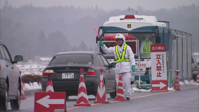 exterior shots of a security guard patrolling cars arriving at a cordoned town a year after a tsunami hit area and caused large scale nuclear... - radiographer stock videos & royalty-free footage