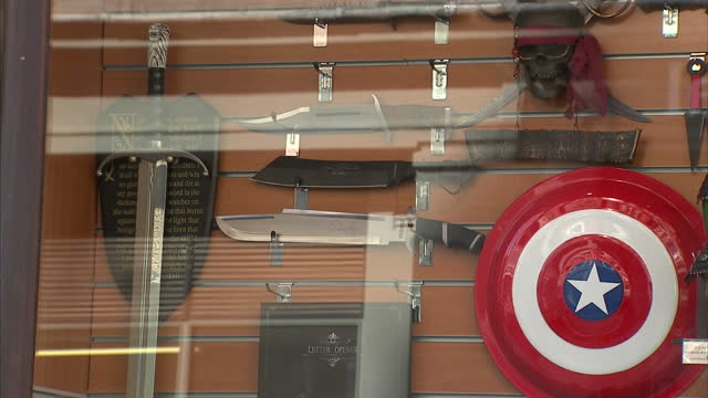 exterior shots of a shop window with a display of knives baseball caps and knick knacks on august 15 2016 in leeds england - kitchen knife stock videos & royalty-free footage