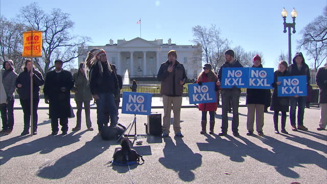 Exterior shots of a small group of protesters in front of the White House holding up placards and making speeches in protest at the controversial...