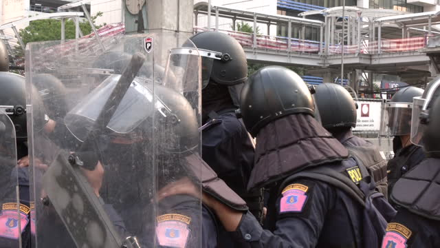 exterior shots of a standoff between police and pro-democracy protesters near the embassy of myanmar with police in riot gear advancing on protesters... - ミャンマー点の映像素材/bロール
