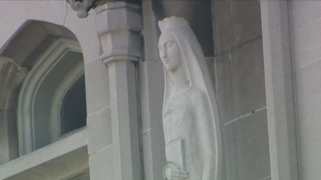 Exterior shots of a stone Mary and Jesus statue outside a Catholic church and windows and gables of church on 15 August 2018 in Erie Pennsylvania...