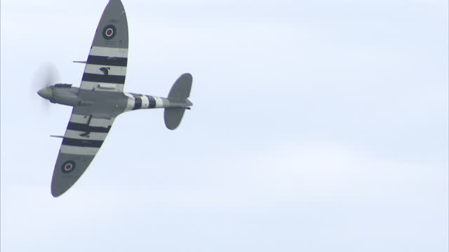 exterior shots of a supermarine spitfire with d-day invasion markings performing a flypast during the sunderland international airshow, followed by... - airshow stock videos & royalty-free footage