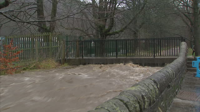 exterior shots of a swollen river in todmorden with water washing over a footbridge and leaking through the stone wall alongside the river>> on... - ウェストヨークシャー点の映像素材/bロール