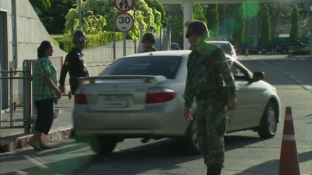 exterior shots of a thai soldier directing traffic on a main road in bangkok and soldiers patroling a checkpoint outside the army club during the may... - directing stock videos and b-roll footage