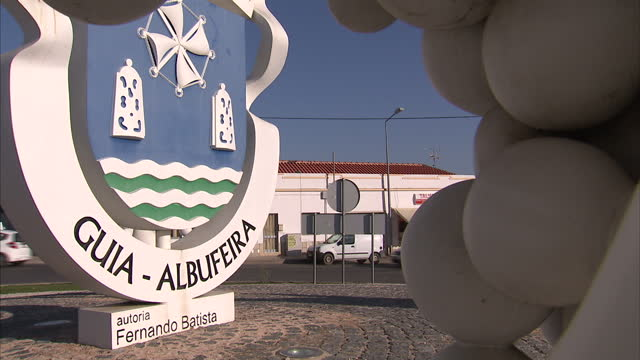 Exterior shots of a town sign for Albufeira on a roundabout with a sculpture depicting a bunch of grapes and wine bottle as the sun sets behind it on...