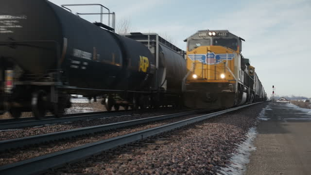 Exterior shots of a very long freight train passing along the tracks in rural Iowa carrying numerous freight cars and flat cars with John Deere...