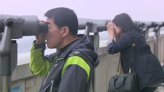 Exterior shots of a viewpoint overlooking the North Korean DMZ as people look through telescopes in dense fog on 18 April 2017 in Imjingak South Korea