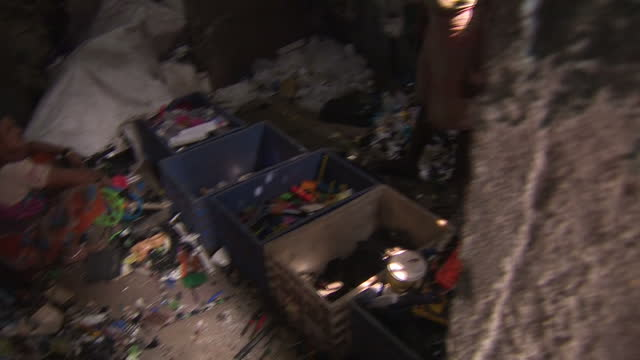stockvideo's en b-roll-footage met exterior shots of a woman in mumbai sorting through plastics in a slum area in order to recycle them on january 24 2017 in mumbai india - afvalverwerking