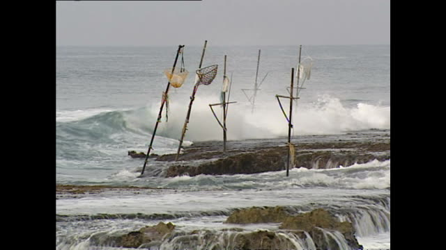 exterior shots of abandoned fishermen's posts and waves crashing on the shoreline in the aftermath of the tsunami in hambantota and a local man... - 2004 indian ocean earthquake and tsunami stock videos & royalty-free footage