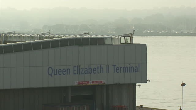 exterior shots of activity around southampton docks including mini cars awaiting export a red funnel isle of wight passenger hyrdrofoil and large... - southampton england stock videos and b-roll footage