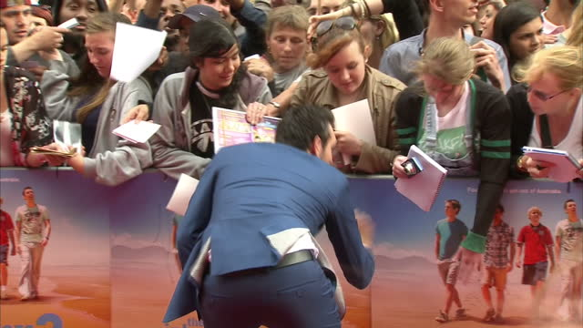 Exterior shots of actor Blake Harrison posing for 'selfies' and signing autographs for fans on the red carpet at the premiere of 'The Inbetweeners...