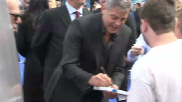 exterior shots of actor George Clooney signing autographs and taking photos with children and disabled people on the blue carpet at the London...