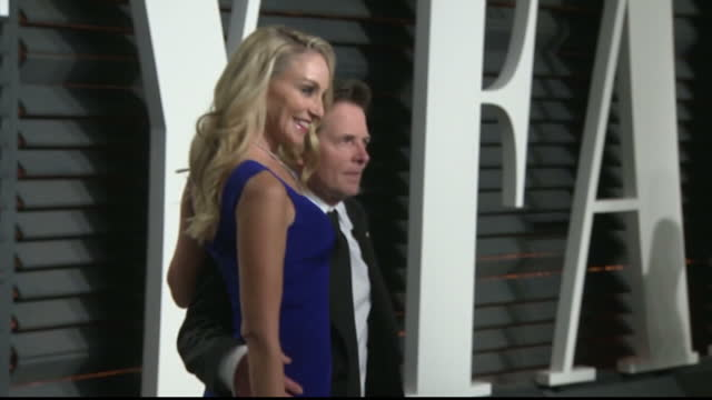 exterior shots of actor michael j fox and his wife tracy pollan posing for photographs as they arrive for the vanity fair oscars party on february 27... - michael j. fox stock videos and b-roll footage